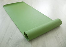 Green yoga carpet. Twisted green yoga carpet on a floor Stock Photography
