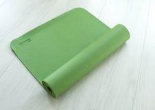Green yoga carpet. Twisted green yoga carpet on a floor Stock Photos