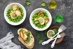 Green young peas, cheese haloumi, lemon. orange salad with slices of bread. Top View.  Royalty Free Stock Image