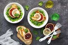Green young peas, cheese haloumi, lemon. orange salad with slices of bread. Top View.  Stock Photography