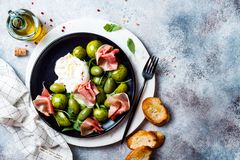 Free Green Zebra Tomatoes And Sliced Burrata Cheese Salad With Fresh Arugula, Prosciutto Or Jamon, Olives And Toasted Bread. Royalty Free Stock Images - 159944069