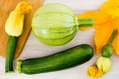 Green zucchini and blossoms. On wooden table royalty free stock images
