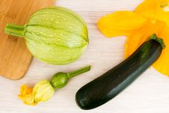 Green zucchini and blossoms. On wooden table royalty free stock photo