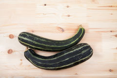 Green zucchini squash lie on a wooden table Stock Images