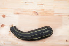 Green zucchini squash lie on a wooden table Royalty Free Stock Image
