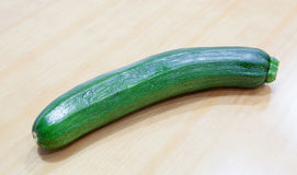 Green zucchini on a wooden surface Royalty Free Stock Photos