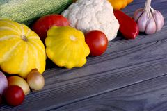 Green zucchini, yellow squash, tomato, cauliflower, bell pepper, onions and garlic. Still-life from seasonal vegetables on a rustic wooden table. Space for your Royalty Free Stock Photo