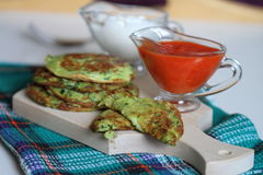 Green zucchinis fritter. With hot sauce and sour cream Royalty Free Stock Images