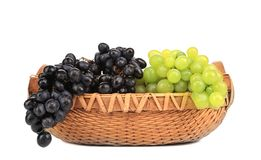 Greenand在篮子的黑色葡萄。 免版税库存照片