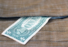 The greenback is in a safe place. One dollar peeking out of surface-mounted pocket-bags Stock Photo
