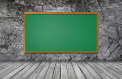Greenboard on wall with wooden table Stock Images