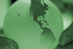 Greenearth. Glass globe of the earth with showing the Americas in a green hue held in tow hands signifying the worlds fate is in your hands Stock Image