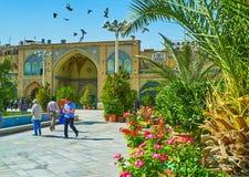 Greenery in courtyard of Shah`s Mosque, Tehran. TEHRAN, IRAN - OCTOBER 11, 2017: The lush garden in courtyard of Shah`s Mosque - the palms, flowers and small Royalty Free Stock Photography