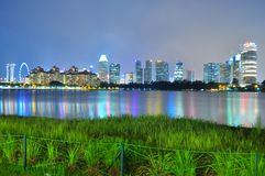 Greenery by Kallang River, with skyline and colourful reflections in the background Royalty Free Stock Photography