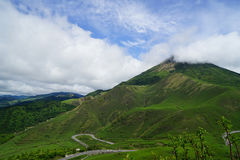 Greenery landscape panorama of Mount Yufu summit with white cloudy sky. Yufuin, Japan Royalty Free Stock Photography