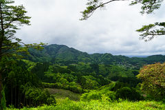 Greenery mountain panorama, town view and sky from afar Stock Photography