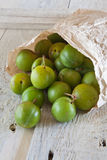 Greengages in a Brown paper Bag. On a white painted rustic background Royalty Free Stock Images