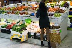 Greengrocer που οργανώνει τα φρούτα και λαχανικά στην αγορά στοκ φωτογραφία