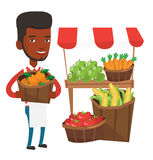Greengrocer with fruits and vegetables. An african-american greengrocer holding basket with oranges. Greengrocer holding basket with fruits. Young happy Royalty Free Stock Image