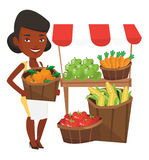 Greengrocer with fruits and vegetables. An african-american greengrocer holding basket with oranges. Greengrocer holding basket with fruits. Young happy Stock Images