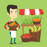 Greengrocer with fruits and vegetables. Asian greengrocer standing near stall with fruits and vegetables. Greengrocer standing near market stall. Greengrocer Stock Image
