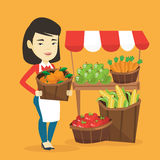 Greengrocer with fruits and vegetables. Asian greengrocer standing near stall with fruits and vegetables. Greengrocer standing near market stall. Greengrocer Stock Photo