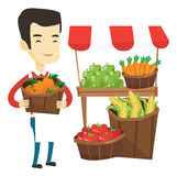 Greengrocer with fruits and vegetables. Greengrocer standing near stall with fruits and vegetables. Greengrocer standing near market stall. Greengrocer holding Royalty Free Stock Photo