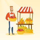 Greengrocer holding box full of apples. Young caucasian greengrocer holding box full of apples. Hipster greengrocer with beard standing in front of grocery Royalty Free Stock Image