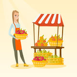 Greengrocer holding box full of apples. Young caucasian greengrocer holding box full of apples. Smiling female greengrocer standing in front of grocery stall Royalty Free Stock Image
