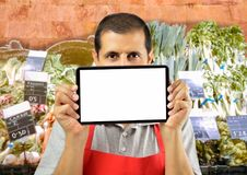 Greengrocer is holding a tablet. Shopman holding tablet over his mouth with copyspace at the greengrocery Royalty Free Stock Photos