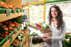 At the greengrocer's. Smiling woman carrying a bag full of food in a supermarket Stock Photo