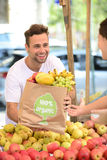 Greengrocer selling organic fruits and vegetables. Royalty Free Stock Images