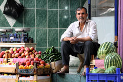 A greengrocer in Urfa in Turkey. A greengrocer sits amongst a variety of fresh produce in his store at the Urfa (Sanliurfa) bazaar in Urfa in south eastern Royalty Free Stock Photos