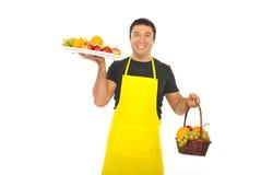 Greengrocerholdinghochebene und -korb mit Früchten Stockfoto