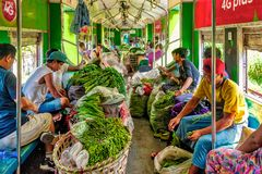 Greengrocers boarding the train with their vegetables. Yangon Circular Railway, Myanmar - Oct. 22, 2017: Local line used by low-incomes, traders, greengrocers stock image