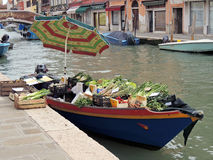 Greengrocery floating on Venetian Canals. Murano, Italy – March 15, 2013: Greengrocery on a small boat floating on the canals of Murano Island in the lagoon of Royalty Free Stock Photos