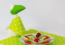 Greenhorn. With bib sits in front of the plate with snacks Stock Images