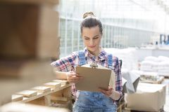 Confident farmer reading report on clipboard during distribution in greenhouse royalty free stock photos