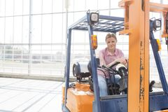 Confident woman sitting in forklift against window in distribution storehouse royalty free stock images