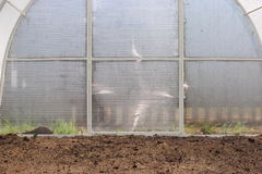 A greenhouse in the garden. With ploughed land Stock Photo