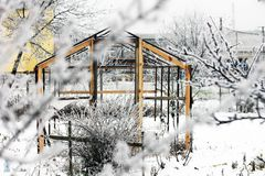 Greenhouse in the snow. Trees in the snow. First snow. Winter. Cold. December. White. Garden.  stock image
