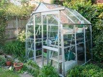Greenhouse. Typical domestic aluminium greenhouse in British garden Royalty Free Stock Photo