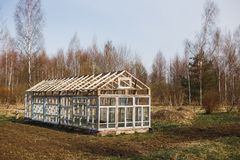 Greenhouse from the windows in the garden in early spring royalty free stock image