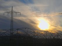 Greenhouses under high-voltage lines in autumn evening royalty free stock images