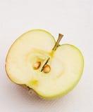 Greenish apple split in half. Royalty Free Stock Image