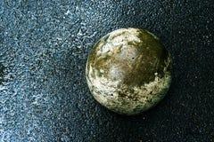 Greenish concrete ball on wet dark asphalt. stock images