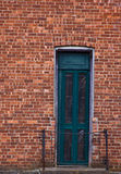 Greenish door on brick Royalty Free Stock Image
