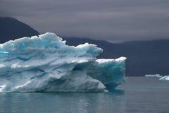 Greenland, błękitna góra lodowa z lightblue punktami inside ono andwith dramatyczny nastrój niebo w atlantyckim oceanie obrazy royalty free