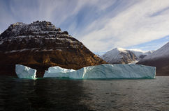 Greenland Iceberg and Fjord - The Artic. Iceberg below mountain peaks in Greenland, looking up the Nerdlerit valley Stock Photography