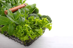 Greens: spinach, cucumber, broccoli, garlic, mint, parsley, lettuce, onions in a metal basket Stock Photo